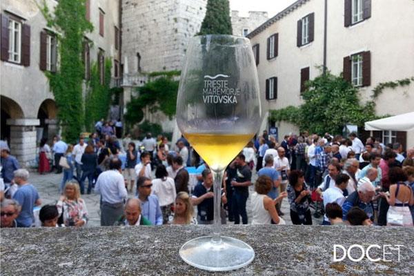Bicchiere di Mare Morje Vitovska su sfondo di castello di Duino
